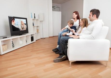 Familie sidder i sofa og ser TV på fladskærm