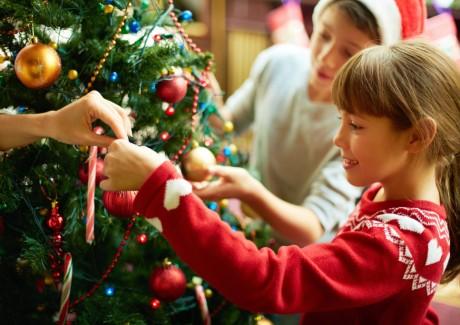 Lille pige hjælper med at pyntejuletræet - jul